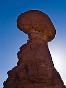 Balanced Rock juts 128 feet/39 meters above the desert floor in Arches National Park, Utah, USA. The Entrada Sandstone at Balanced Rock (128 feet/39 meters high) balances a caprock of the hard Slick Rock Member upon a base of the Dewey Bridge Member, a mudstone.