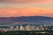 Reno, Nevada, downtown city skyline with casinos and mountains in the background at sunset