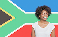 Young African American woman in white t-shirt smiling against South African flag