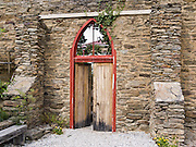 Old weathered wood door with red orange frame and arched window top enters a stone wall at Clyde, South Island, New Zealand.