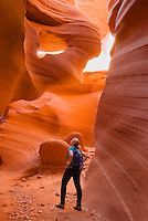 A hiker explores the sandstone slots of the Lower Antelope Canyon, Lake Powell Navajo Tribal Park, Arizona.