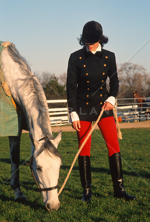 Woman in riding gear holding a rope and a white horse in Southampton, NY