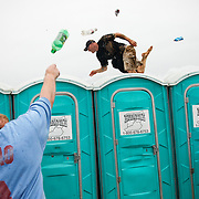 An infield partier slips and falls on the slippery plastic roofs as he dodged beer cans thrown at him while running across a line of portable restrooms and a gauntlet of projectiles during the 136th running of the Kentucky Derby at Churchill Downs Saturday May 1, 2010. Photo by David Stephenson