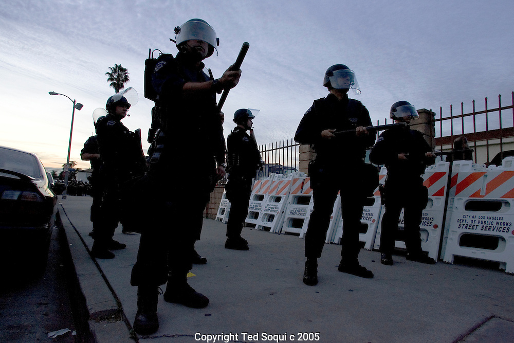 """LAPD officers set up a perimeter after gang members shoot bullets into the air at the Funeral services for Stanley """"Tookie"""" Williams at Bethel A.M.E. Church in S. Central LA. About 2000 people attended the services which included many gang members. The funeral was a star studded event attended by Jesse Jackson and rapper-actor Snoop Dogg, Nation of Islam leader Louis Farrakhan, and Bianca Jagger.  Loudspeakers and a large TV screen brought the service to many of the onlookers who could not get inside the packed church..."""