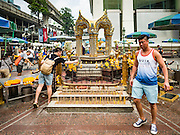 16 AUGUST 2016 - BANGKOK, THAILAND: A tourist walks around Erawan Shrine one year after the shrine was bombed in the worst international terrorist attack in Thai history. On 17 August 2015, a bomb was set off at the Erawan Shrine, a popular tourist attraction and important religious shrine in the heart of the Bangkok shopping district. According to the Royal Thai Police  20 people were killed in the bombing and 125 injured. Most of the people killed in the bombing were tourists from other countries in Asia. Thai Police arrested an alleged Uighur extremist for the bombing. The case against him is still pending in Thai courts. The shrine was repaired, rededicated and reopened to the public on 4 September 2015.      PHOTO BY JACK KURTZ
