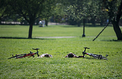 © Licensed to London News Pictures. 15/04/2020. London, UK. Two women with bikes, sunbathing on Primrose Hill, North London, during a pandemic outbreak of the Coronavirus COVID-19 disease. The public have been told they can only leave their homes when absolutely essential, in an attempt to fight the spread of coronavirus COVID-19 disease. Photo credit: Ben Cawthra/LNP