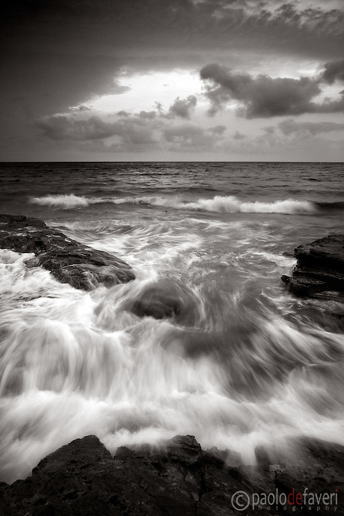 The rising tide of mid of September, intensified by the northwestern wind known as Mistral, at sunset. Taken on a evening of mid September on the rocky coast near to Barcaggio, Cap Corse, Corsica, France.
