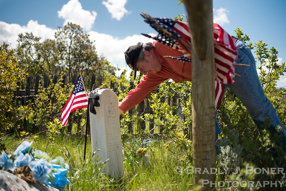 Korean War veteran Wayne Flittner places a flag at Kelly Cemetery on the grave stone of Ben Seaton, who fought in World War I. The Kelly Cemetery has grave sites for several well-known Jackson Hole families, including the Seatons, Taylors and Shinkles.