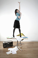 Woman standing on desk and singing
