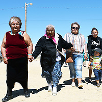 Daughters, granddaughters and great-grandchildren of Adza'a'ilchi Mitchell walk to her home in Little Water for a family portrait.