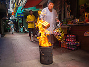 "10 AUGUST 2014 - BANGKOK, THAILAND:     A woman burns joss paper and hell money on the first day of Ghost Month in a back alley in Bangkok's Chinatown. The seventh month of the Chinese Lunar calendar is called ""Ghost Month"" during which ghosts and spirits, including those of the deceased ancestors, come out from the lower realm. It is common for Chinese people to make merit during the month by burning ""hell money"" and presenting food to the ghosts.  PHOTO BY JACK KURTZ"