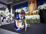 16 OCTOBER 2016 - BANGKOK, THAILAND:  A worker cleans the carpet in front of a shrine for Thai King Bhumibol Adulyadej who died Oct. 13, 2016. He was 88. His death comes after a period of failing health. With the king's death, the world's longest-reigning monarch is Queen Elizabeth II, who ascended to the British throne in 1952. Bhumibol Adulyadej, was born in Cambridge, MA, on 5 December 1927. He was the ninth monarch of Thailand from the Chakri Dynasty and is known as Rama IX. He became King on June 9, 1946 and served as King of Thailand for 70 years, 126 days. He was, at the time of his death, the world's longest-serving head of state and the longest-reigning monarch in Thai history.          PHOTO BY JACK KURTZ