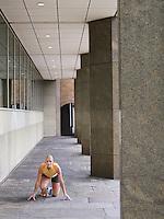 Female athelete crouching on pavement by pillars
