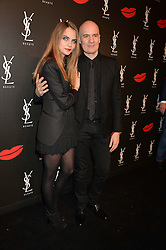 CARA DELEVINGNE and STEPHAN BEZY the international general manager of Yves Saint Laurent Beauté at L'Oréal at the YSL Beauty: YSL Loves Your Lips party held at The Boiler House,The Old Truman Brewery, Brick Lane,London on 20th January 2015.