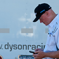July 6, 2012 - Dyson Racing chief Rob Dyson checks his phone behind the team trailer during the American Le Mans Northeast Grand Prix weekend at Lime Rock Park in Lakeville, Conn.