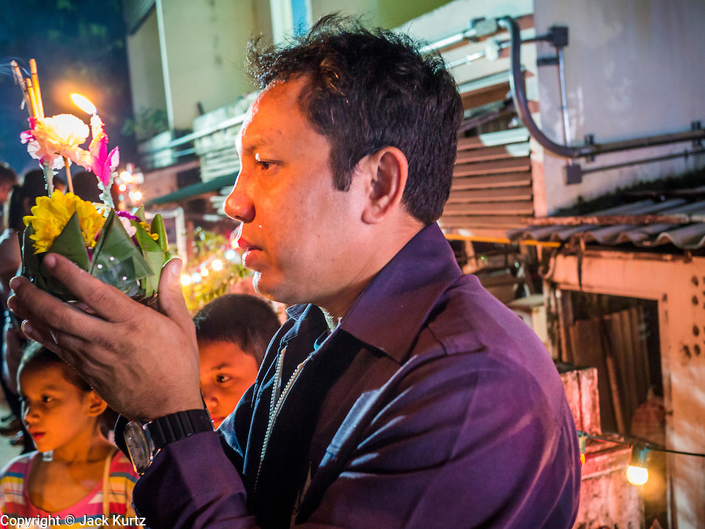 28 NOVEMBER 2012 - BANGKOK, THAILAND: A man prays before launching his krathong on Loy Krathong at Wat Yannawa in Bangkok. Loy Krathong takes place on the evening of the full moon of the 12th month in the traditional Thai lunar calendar. In the western calendar this usually falls in November. Loy means 'to float', while krathong refers to the usually lotus-shaped container which floats on the water. Traditional krathongs are made of the layers of the trunk of a banana tree or a spider lily plant. Now, many people use krathongs of baked bread which disintegrate in the water and feed the fish. A krathong is decorated with elaborately folded banana leaves, incense sticks, and a candle. A small coin is sometimes included as an offering to the river spirits. On the night of the full moon, Thais launch their krathong on a river, canal or a pond, making a wish as they do so.    PHOTO BY JACK KURTZ