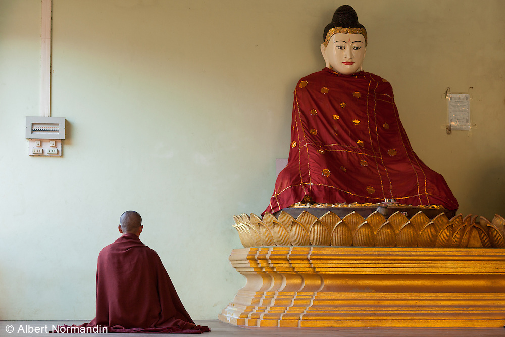 Monk in moment of Meditation in front of Buddha Statue at Shwemawdaw Pagoda