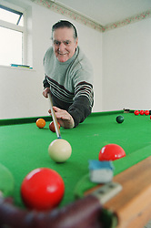 Elderly man with Alzheimer's disease playing game of snooker,