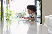 Boy (5-6 years) using laptop in dining room side view