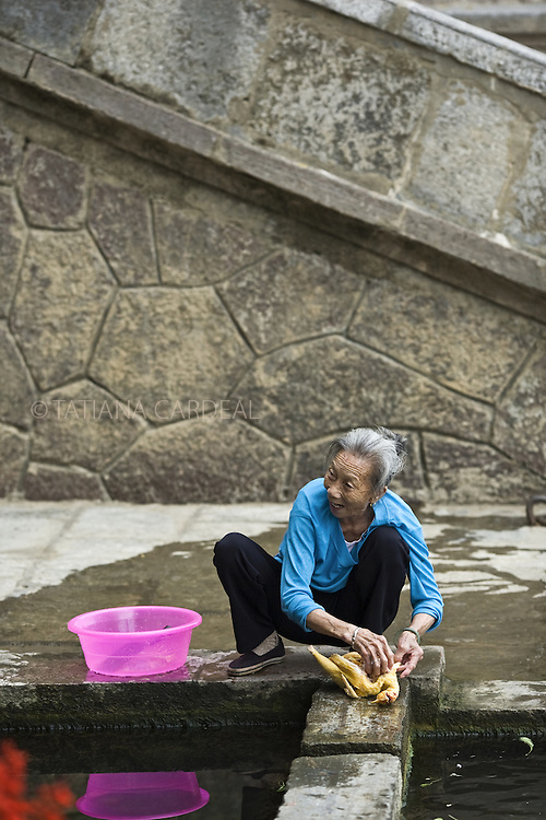 Old woman washes a chicken to cook.