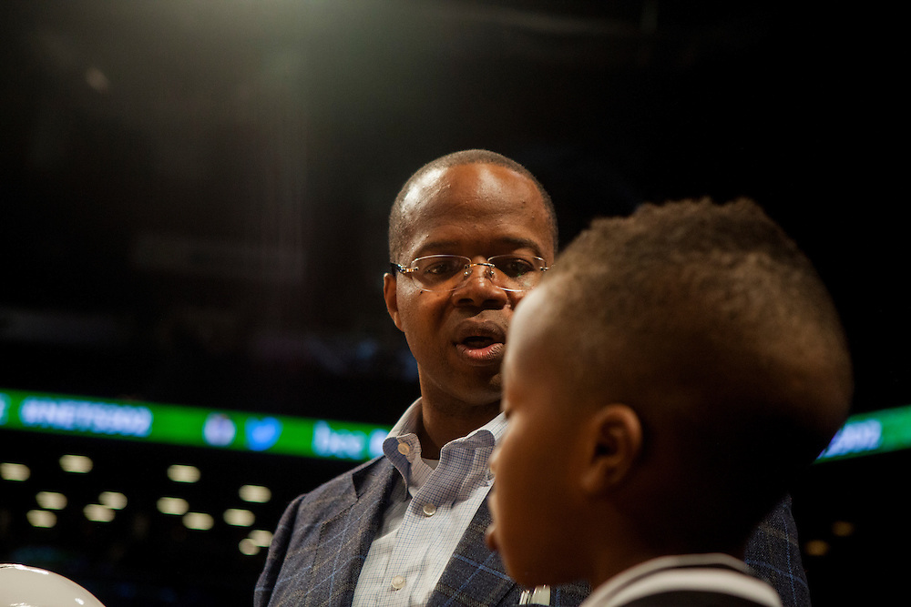 BROOKLYN, NY - MARCH 2, 2015:   Brooklyn District Attorney Kenneth P. Thompson hangs out with his son Kenny before a game between the Brooklyn Nets and the Golden State Warriors at the Barclay's Center.
