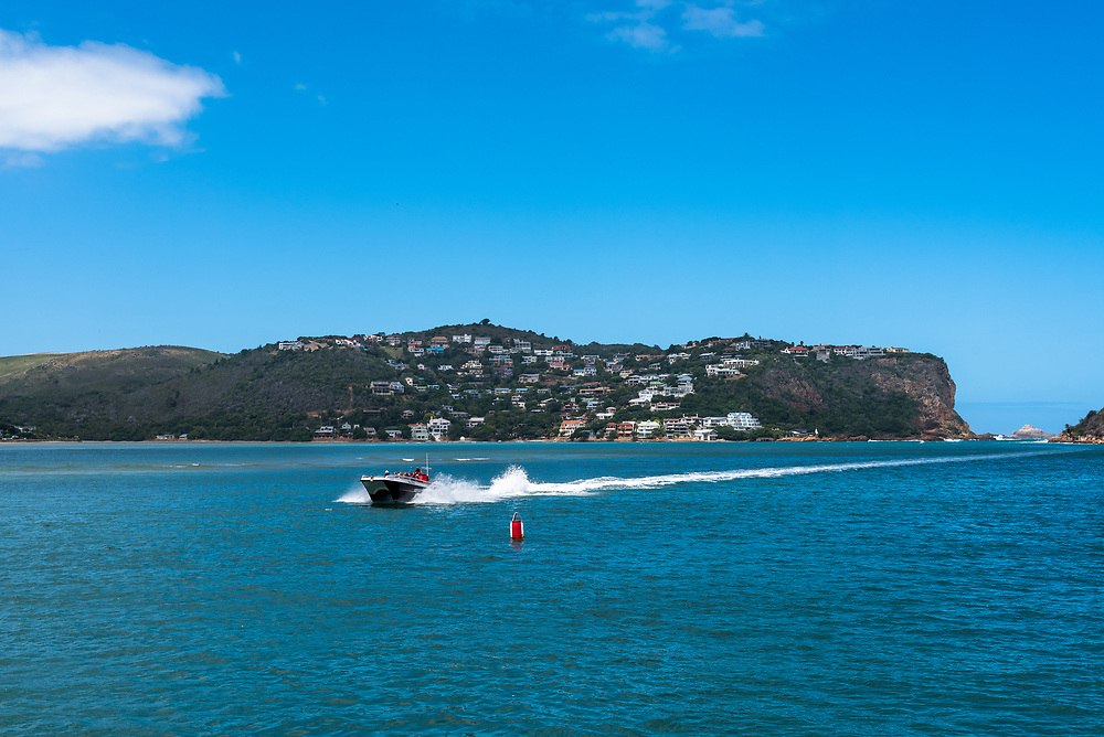 Mossel Bay, South Africa--January 10, 2018--A motorboat speeds along Knysna Lagoon leaving a wake behind it. Editorial use only.