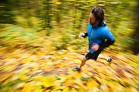 A high angle panning view of a man trail running in fall colors.