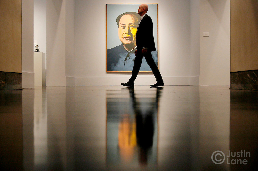 epa00862406 A man walks past Andy Warhol's painting 'Mao' during a preview of an auction of post-war and contemporary art Christie's auction house in New York on Tuesday 14 November 2006. The auction is scheduled for 15 and 16 November 2006, and the painting is expected to sell for at least $12 million (USD).  EPA/JUSTIN LANE