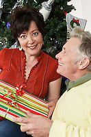 Senior couple holding present in front of Christmas tree