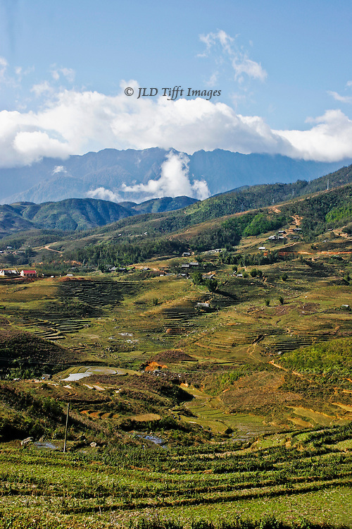 Landscape of the hilly farmland near Sa Pa, North Vietnam.  Expansive vertical view toward distant mountains and clouds.