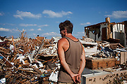 A man named Mark surveys the scene where his friend's mother's home used to stand in Joplin, Missouri on Friday, June 24, 2011. The elderly woman had been moved into a extended care facility shortly before the sudden tornado wiped out her home. The tornado was a catastrophic EF5 multiple-vortex tornado on Sunday, May 22, 2011. The storm killed 158 people and resulted in $2.8 billion dollars in damage.