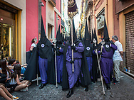 A procession proceeds solemny in Calle Cuna a main street in the centre of Seville, heading towards the Cathedral. Andalusia, Spain.