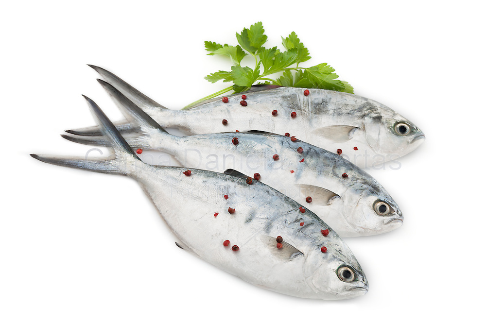 Raw trevally fish with parsley and red peppercorns, isolated on white background.