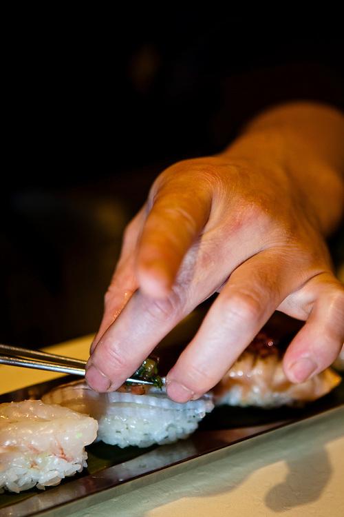 Chef Noriaki Yasutake carefully places a garnish on a piece of sushi.