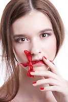 Portrait of beautiful young woman with red ribbon tied over mouth against white background