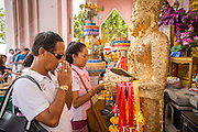 12 OCTOBER 2012 - NAKHON PATHOM, NAKHON PATHOM, THAILAND:  People pray and apply gold leaf to Buddha statues to make merit Phra Pathom Chedi in Nakhon Pathom. The Phra Pathom Chedi in Nakhon Pathom was commissioned by King Mongkut and completed by King Chulalongkorn in 1870. The chedi is 127 meters tall and is one of the tallest pagodas in the world. It is located in the center of the city of Nakhon Pathom and has been an important Buddhist center since the 6th century. According to local history, Nakhon Pathom is where Buddhism first came to Thailand.     PHOTO BY JACK KURTZ