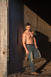 shirtless muscular man in a rustic barn