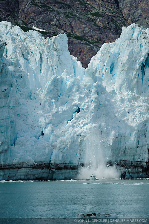 """A portion of the face of Margerie Glacier, one of the seven tidewater glaciers in Glacier Bay National Park and Reserve in southeast Alaska collapses with a loud rifle sounding """"crack"""" and booming roar. The Margerie Glacier is located on the Tarr Inlet next to another tidewater glacier, Grand Pacific Glacier. Margerie Glacier's one mile wide face has a total height of 350 feet, out of which 250 feet is above the water level and 100 feet is beneath the water surface. For comparison purposes the Statue of Liberty is 307 feet tall. The length of the glacier (2011) is approximately 21 miles."""