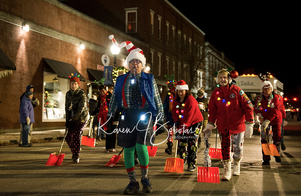 "Larry Frates leads the Taylor Community ""Shovel Brigade"" down Main Street during the ""Light Up Laconia"" Holiday Parade Sunday evening.  (Karen Bobotas/for the Laconia Daily Sun)"