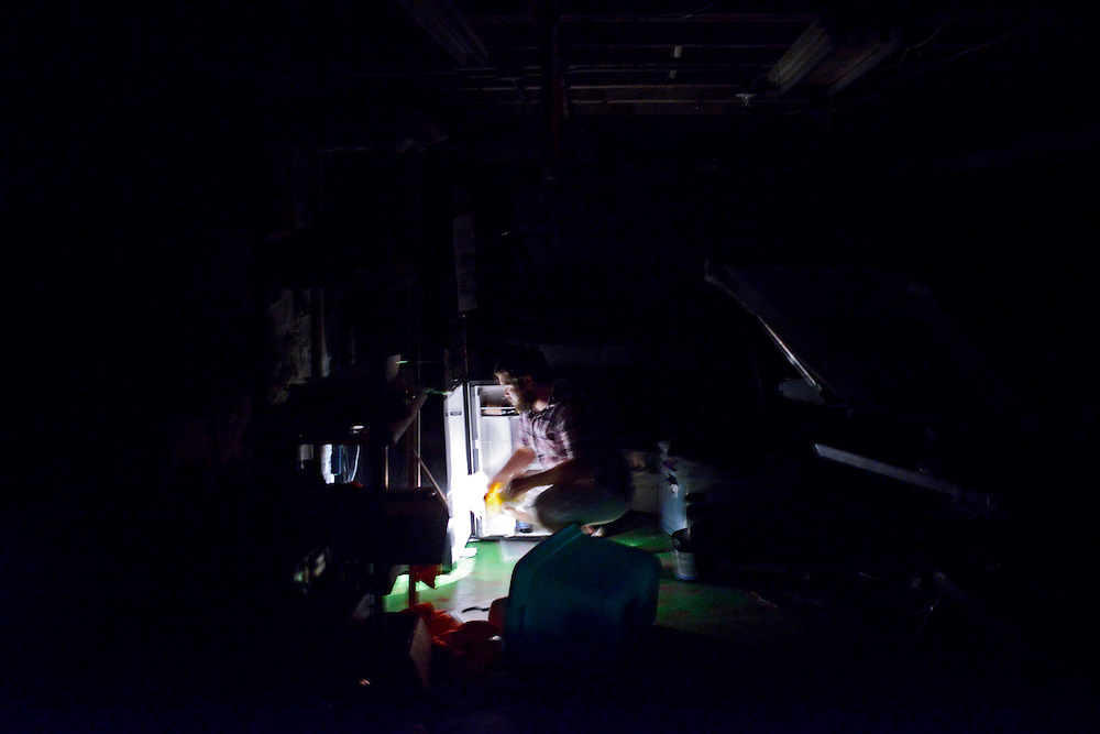 (photo by Matt Roth).Assignment ID: 30128227A..Matt Fouse uses a flashlight to look for a beer in the refrigerator in his basement, the coolest part of his house, on the 3200 block of Abell Ave in Baltimore, MD Saturday, June 30, 2012. ...After a deadly storm swept through the Mid-Atlantic region Friday night, over three million in Maryland, Virginia, West Virginia, Ohio, and Washington D.C. are without power during a heat wave. In Maryland temperatures stayed in the 90's and 100's. .