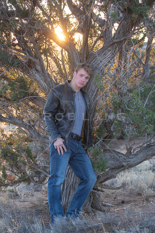 man in a leather jacket leaning against a  Tree at sunset