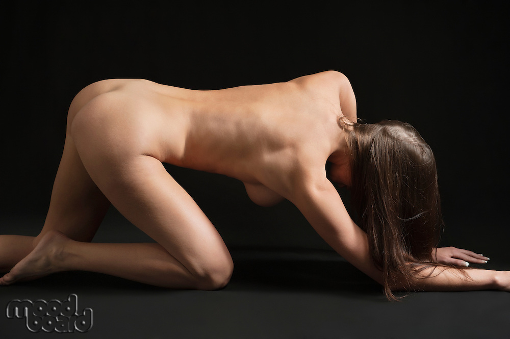 Back view of naked woman crawling on hands and knees over black background