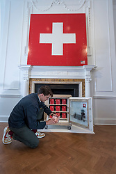 """© Licensed to London News Pictures. 05/10/2018. LONDON, UK. An artist's assistant next to a passport vault. Preview of """"Swiss Passport Office"""" by American artist Tom Sachs at Galerie Thaddaeus Ropac in Mayfair.  To coincide with Frieze Week, the gallery will remain open for 24 hours from 6pm 5 October to 6pm 7 October for the issuing of serial-numbered Tom Sachs Swiss passports for visitors.  The installation reflects the concerns relating to Brexit, Syria and Donald Trump's immigration policies and challenges the notion of global citizenship.  Photo credit: Stephen Chung/LNP"""