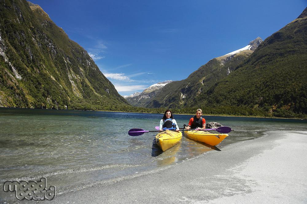 Two people in kayaks near shore of mountain lake