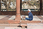 INDIA, OLD DELHI:  Devout East Indian Muslim man reading the Quran in the courtyard of the Jama Masjid Mosque as he waits for prayer time.
