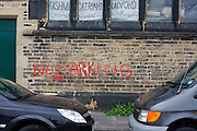 Two cars have been parked beneath the words No Parking which have been painted by hand on industrial bricks of a wall in a quiet street off Lumb Lane near Bradford city centre, Yorkshire. Above the message in the window is both Kashmiri and English writing for a mis-spelled business called Kashmir Catring Bradford.