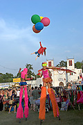 Two stilt performers and the artist Bansky, with his trademark girl with balloons, walk past the Chapel of love & loathing in Lost Vagueness at the Glastonbury Festival.