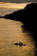 Indians crossing the Amazon River at sunset - Peru.