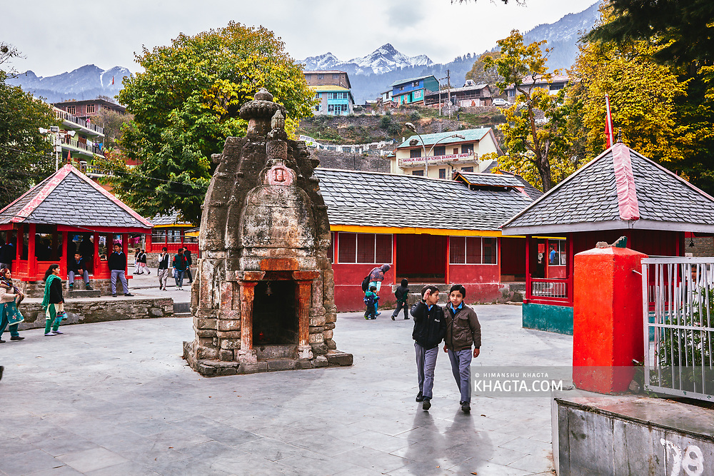 School kids walk in front of an ancient temple in Chaurasi temple complex in Bharmaur, Chamba, Himachal Pradesh, India
