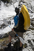 Man carrying kayak, looking at river, back view